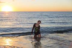 Mujer joven que salpica en el océano imagenes de archivo