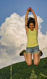 Mujer joven que salta arriba en las montañas Imágenes de archivo libres de regalías