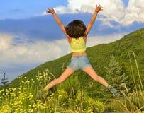 Mujer joven que salta arriba en las montañas Foto de archivo libre de regalías