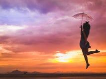 Mujer joven que salta con el paraguas en la puesta del sol fotografía de archivo libre de regalías