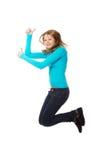 Mujer joven que salta con los pulgares para arriba Imágenes de archivo libres de regalías