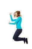 Mujer joven que salta con los pulgares para arriba Foto de archivo