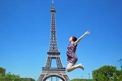 Mujer joven que salta contra torre Eiffel imagen de archivo