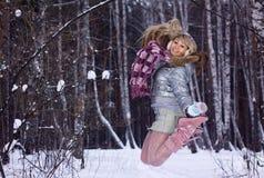 Mujer joven que salta en bosque del invierno Foto de archivo