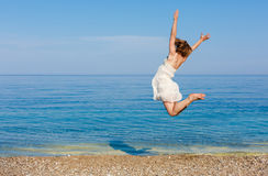 Mujer joven que salta en la playa Fotografía de archivo