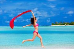 Mujer joven que salta en la playa con una bufanda roja fotos de archivo libres de regalías
