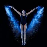 Mujer joven que salta en nube azul del polvo Fotos de archivo libres de regalías
