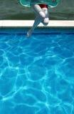 Mujer joven que salta en piscina Imagen de archivo