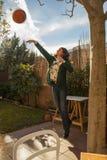 Mujer joven que salta mientras que juega la cesta en el patio trasero asoleado Foto de archivo libre de regalías