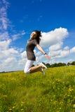 Mujer joven que salta para la alegría en el aire Imagen de archivo