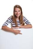 Mujer joven que señala abajo a un letrero Imagenes de archivo