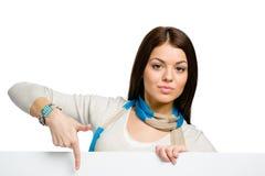 Mujer joven que señala con el índice en el copyspace Imagenes de archivo