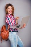 Mujer joven que señala el finger en la pantalla del ordenador portátil Imagen de archivo libre de regalías