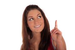 Mujer joven que señala en algo Foto de archivo