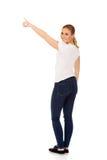 Mujer joven que señala en espacio o algo de la copia Fotos de archivo