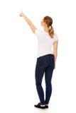 Mujer joven que señala en espacio o algo de la copia Fotos de archivo libres de regalías
