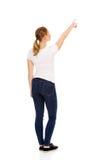 Mujer joven que señala en espacio o algo de la copia Foto de archivo libre de regalías