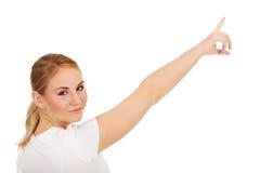 Mujer joven que señala en espacio o algo de la copia Imágenes de archivo libres de regalías