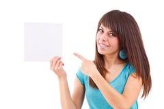 Mujer joven que señala en la tarjeta en blanco en su mano Fotos de archivo libres de regalías