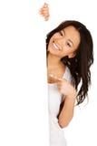 Mujer joven que señala en tablero en blanco Fotografía de archivo libre de regalías