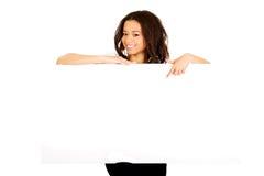 Mujer joven que señala en tablero en blanco Imagenes de archivo
