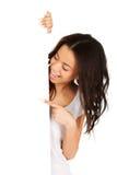 Mujer joven que señala en tablero en blanco Fotos de archivo libres de regalías