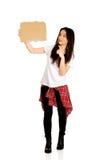 Mujer joven que señala en una cartulina Fotografía de archivo libre de regalías