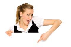 Mujer joven que señala en una tarjeta en blanco Fotos de archivo libres de regalías