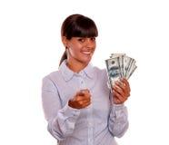 Mujer joven que señala en usted y que lleva a cabo dólares Fotos de archivo libres de regalías