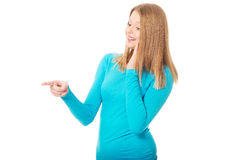 Mujer joven que señala a la izquierda Imágenes de archivo libres de regalías