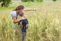 Mujer joven que señala la mano y al niño pequeño su hijo que se coloca en whe imagen de archivo