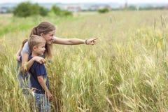 Mujer joven que señala la mano y al niño pequeño su hijo que se coloca en whe Fotos de archivo