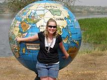 Mujer joven que señala a la trayectoria del viaje en mapa gigante  Foto de archivo