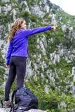 Mujer joven que señala mientras que se opone en una roca a sorprender foto de archivo libre de regalías
