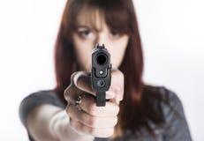 Mujer joven que señala un arma en la cámara Imágenes de archivo libres de regalías