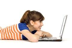 Mujer joven que se acuesta con la computadora portátil Foto de archivo