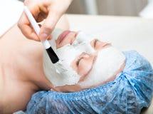 Mujer joven que se acuesta en un salón del balneario y que tiene un tratamiento facial de la belleza Los procedimientos cosmético Imagen de archivo