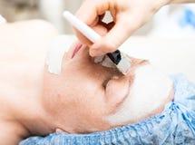 Mujer joven que se acuesta en un salón del balneario y que tiene un tratamiento facial de la belleza Los procedimientos cosmético Imagenes de archivo