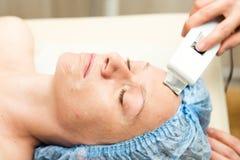Mujer joven que se acuesta en un salón del balneario y que tiene una limpieza ultrasónica de la cara Los procedimientos cosmético Imagen de archivo
