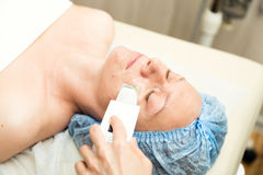 Mujer joven que se acuesta en un salón del balneario y que tiene una limpieza ultrasónica de la cara Los procedimientos cosmético Fotos de archivo libres de regalías
