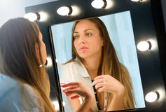 Mujer joven que se admira en el espejo Imagen de archivo