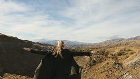 Mujer joven que se coloca al borde del acantilado y que aumenta sus manos para arriba contra las altas montañas rocosas que toman metrajes