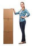 Mujer joven que se coloca al lado de la torre de cajas imagen de archivo libre de regalías