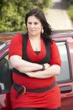 Mujer joven que se coloca al lado del coche Foto de archivo libre de regalías