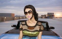 Mujer joven que se coloca al lado del coche convertible Foto de archivo