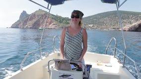 Mujer joven que se coloca al mando de la motora Mar almacen de video