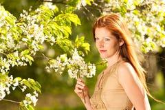 Mujer joven que se coloca bajo cerezo floreciente Imágenes de archivo libres de regalías