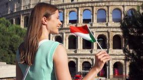 Mujer joven que se coloca cerca de Colosseum en Roma, Italia Adolescente que agita la bandera italiana en la cámara lenta