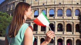 Mujer joven que se coloca cerca de Colosseum en Roma, Italia Adolescente que agita la bandera italiana en la cámara lenta almacen de metraje de vídeo