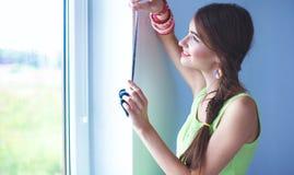 Mujer joven que se coloca cerca de la pared oscura, mirando la ventana Foto de archivo